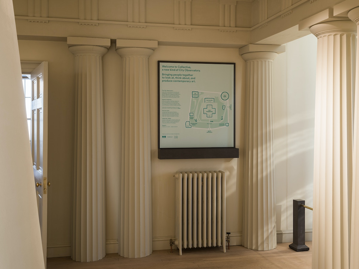 A room with columns lining the walls. A large map of the Collective site hangs on the wall.