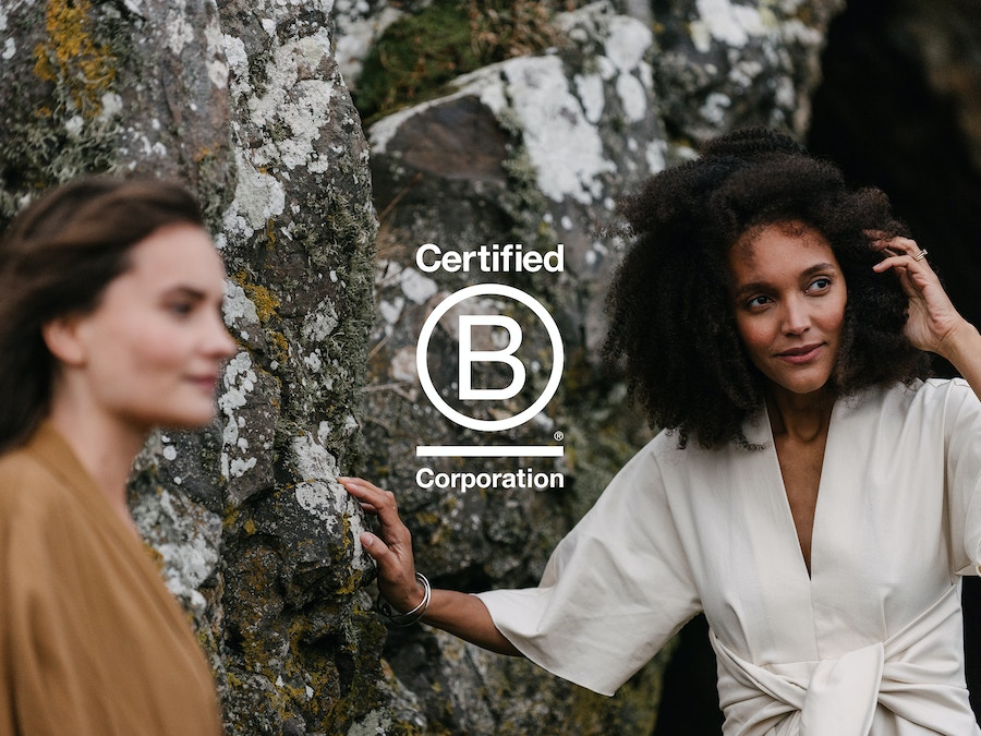 Two women standing in front of rocks. The B Corp logo has been placed on top.