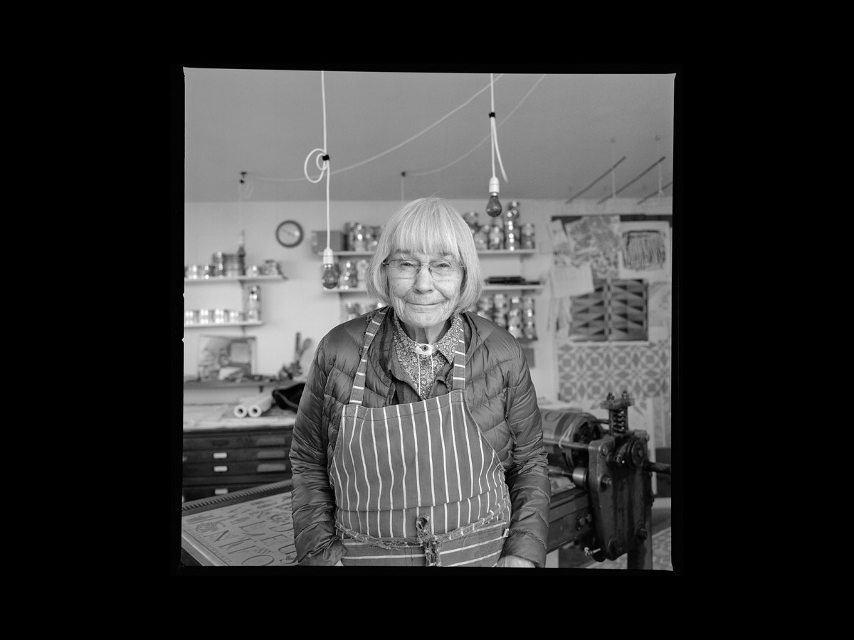 An older lady standing with a striped apron on. She has grey hair and stares at the camera.