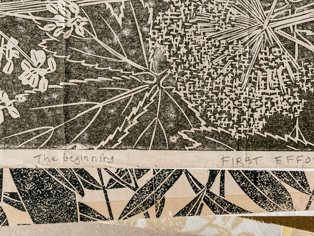 """Different botanical shapes made in black and cream. There is text just below the middle that reads """"The beginning"""" """"First Effort"""""""
