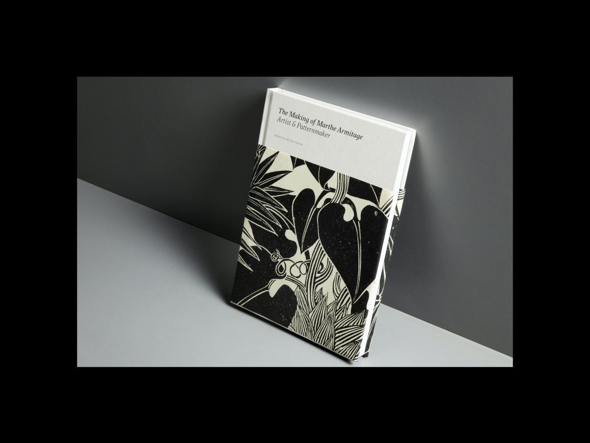 A book sits leaning against a dark grey background. The book has a black and cream patterned wrap-around cover on it.