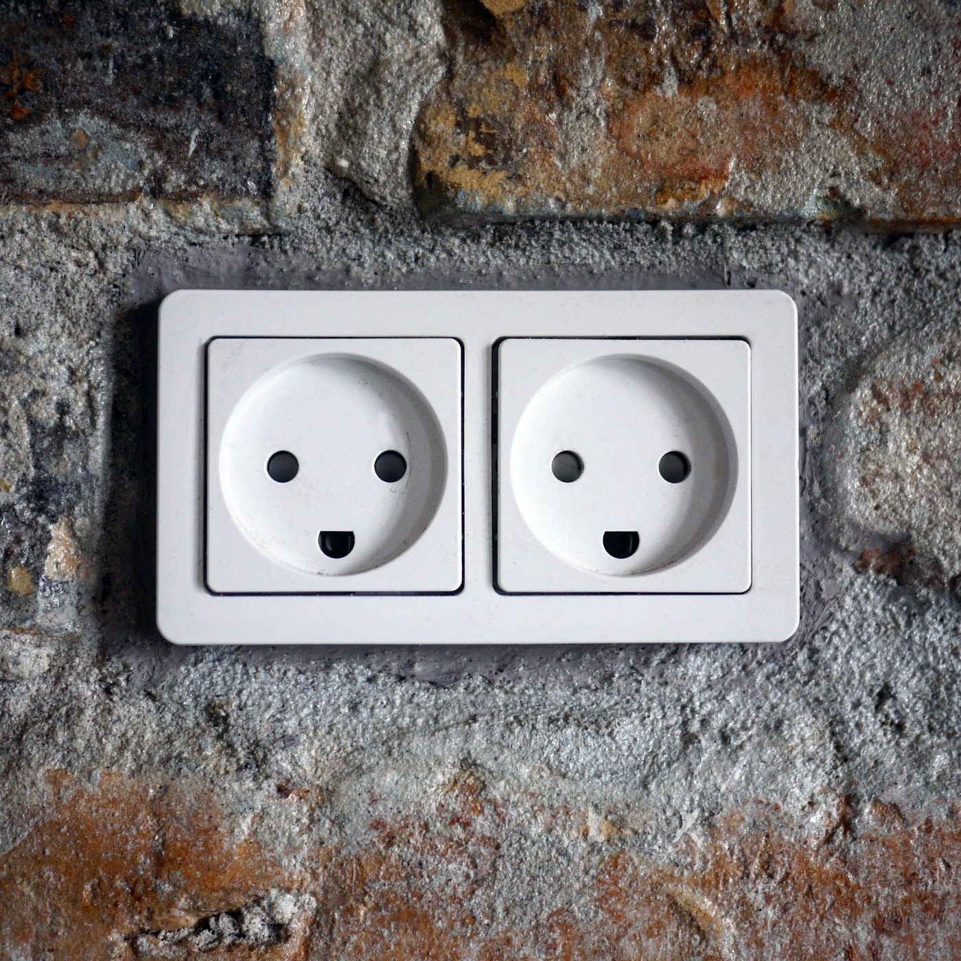 Two white plugs with holes that form a smiling face