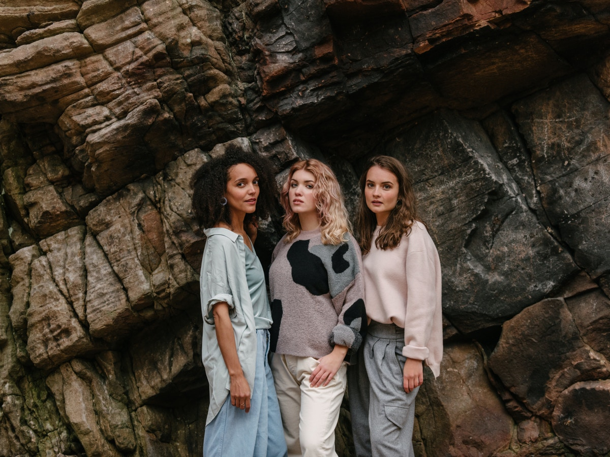 Three women standing close together in front of a rock face. They are all looking at the camera.