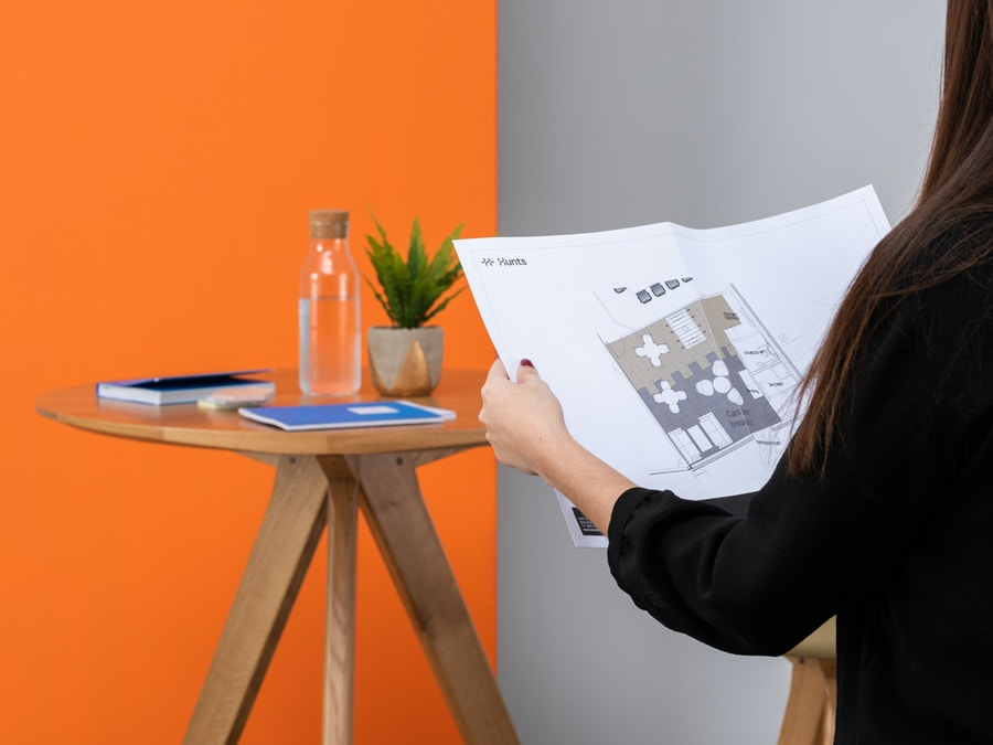 A women reading a floor plan. There is a wooden coffee table with a book and water carafe on it.