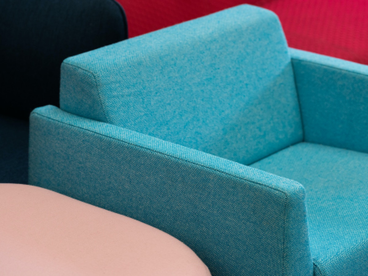 A blue armchair. There is a pink piece of furniture to its left.