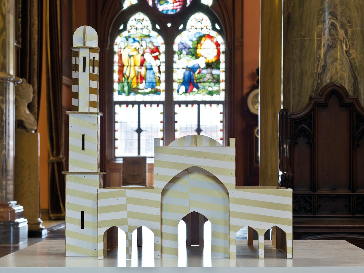 A small model of church in front of a stained glass window.