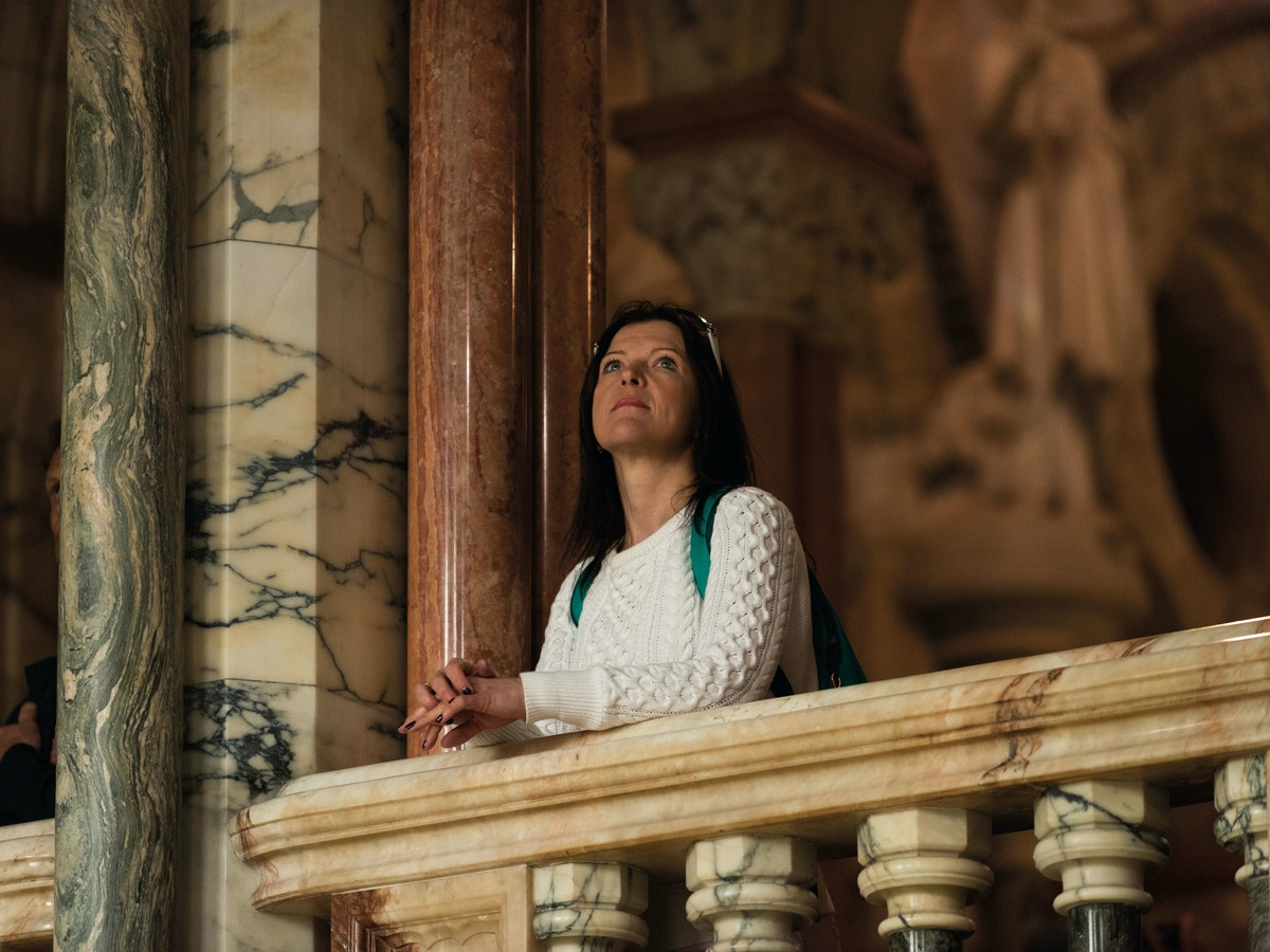 Lady standing at a balcony in a marble church.