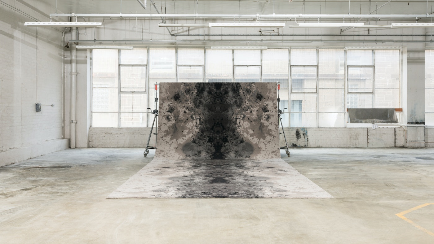 A large carpet swooping up from the floor onto a metal bar in front some windows.