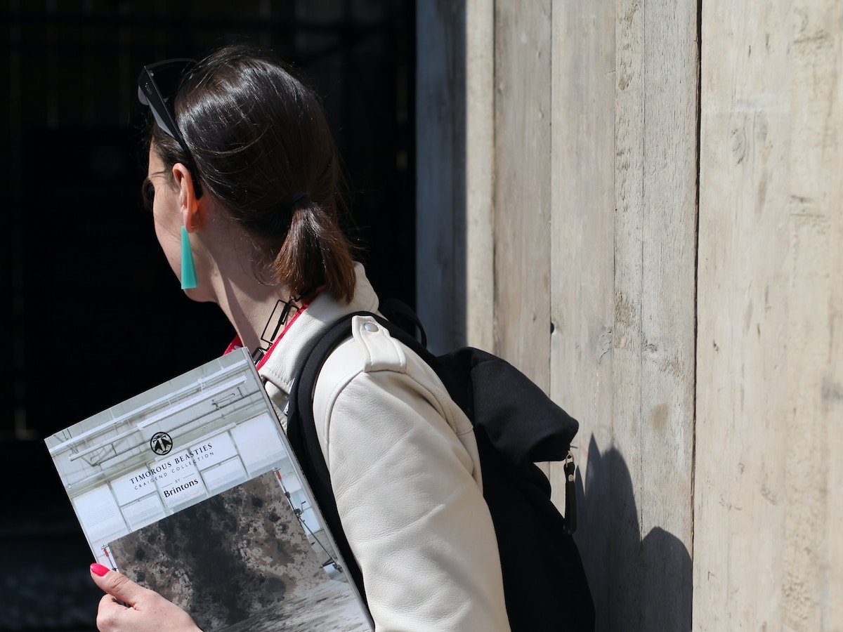 A woman turning away from the camera holding a catalogue. She is wearing a beige coat and a black backpack.