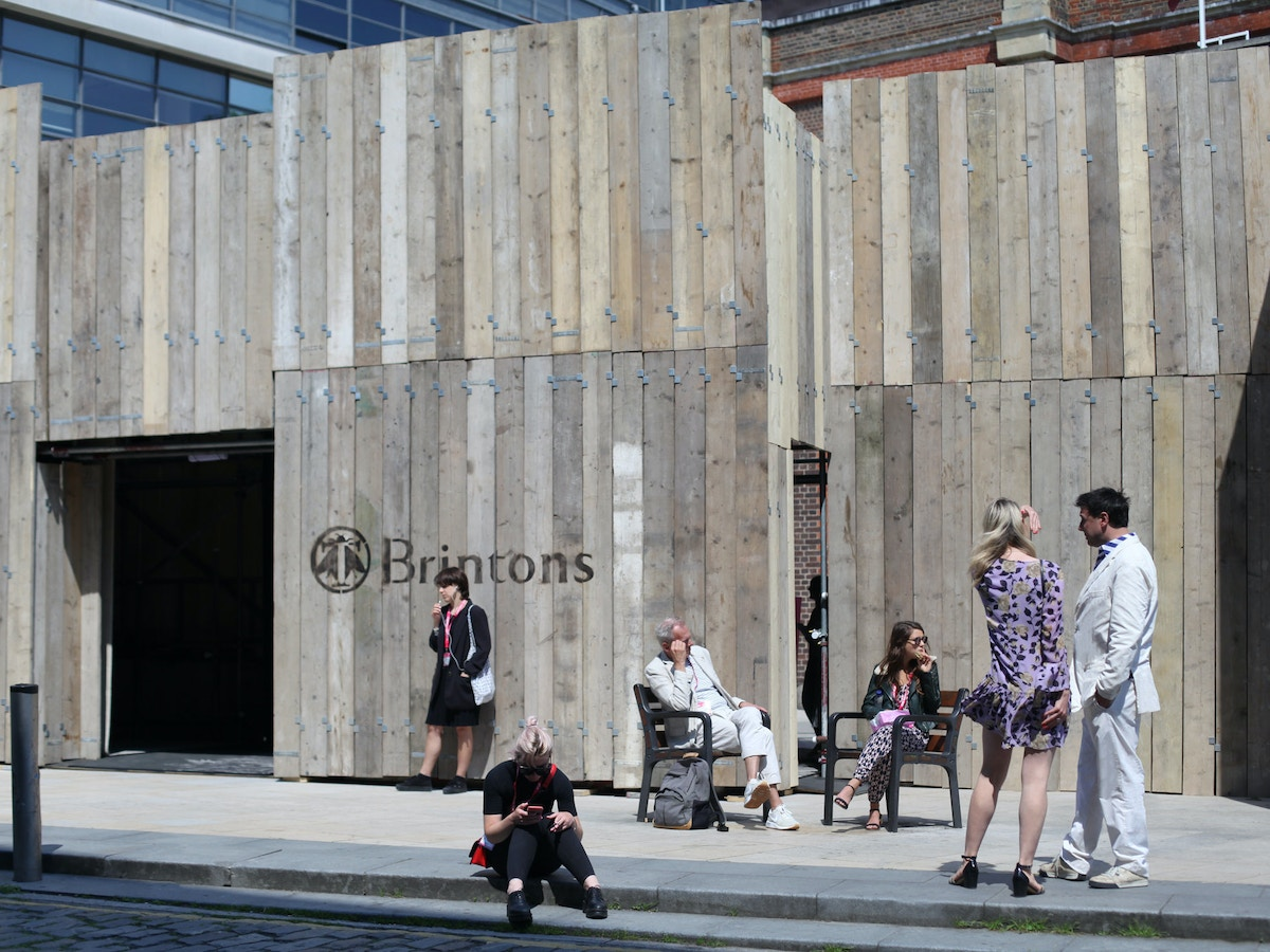 People standing outside of a wooden structure in the sunshine.