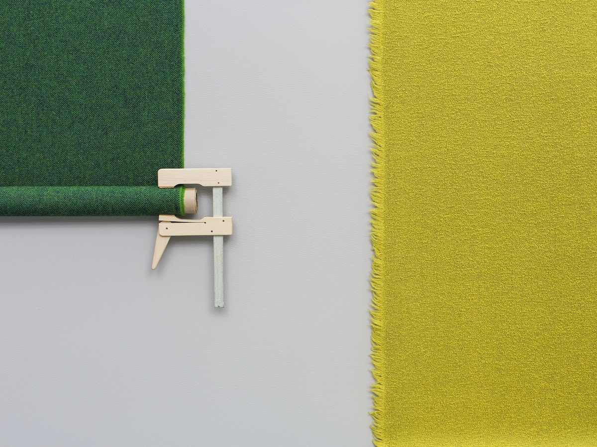 A wooden clasp holding onto the bottom of a green roll of fabric. There is a yellow piece of fabric to the right.