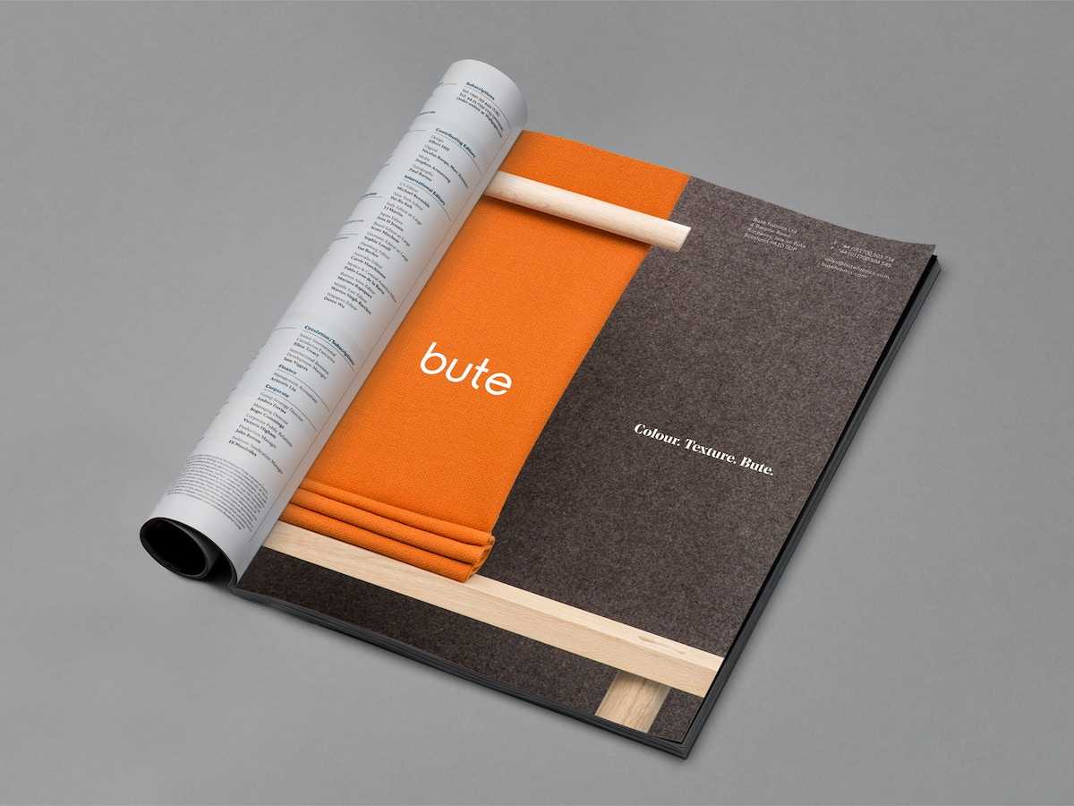 A printed magazine advert that shows a piece of a wooden structure with orange fabric in the background.