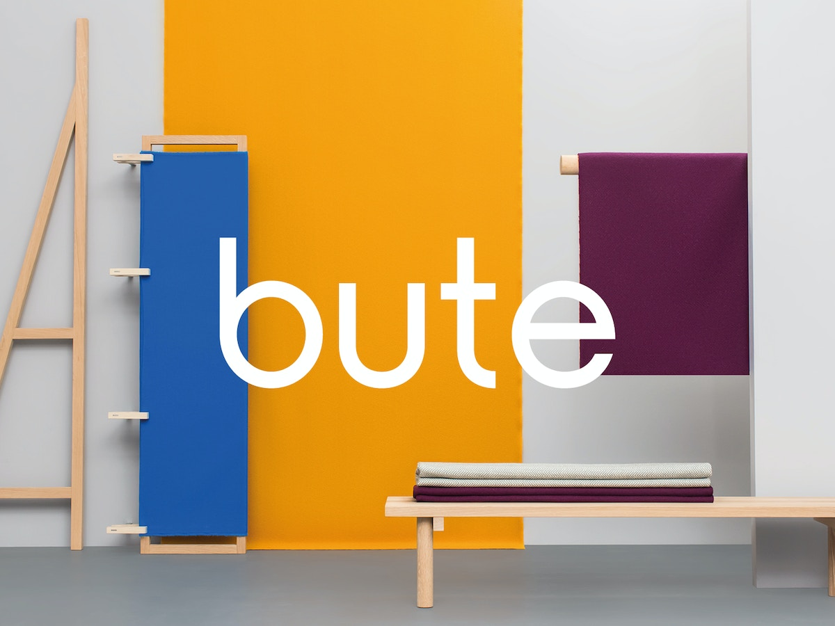 "A piece of text that reads ""bute"" in front of a set up that includes wooden structures and large pieces of fabric."