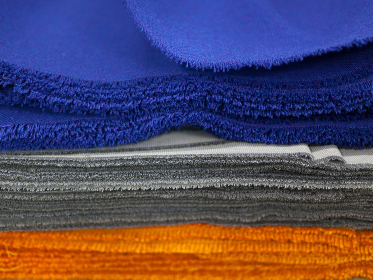 Orange, Grey and Blue fabric piled on top of each other.