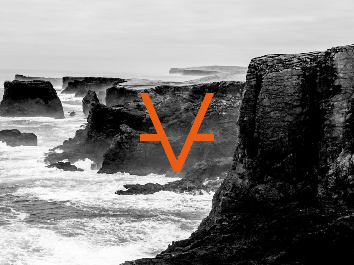 Cliff face with crashing waves in black and white. There is an orange V on top.