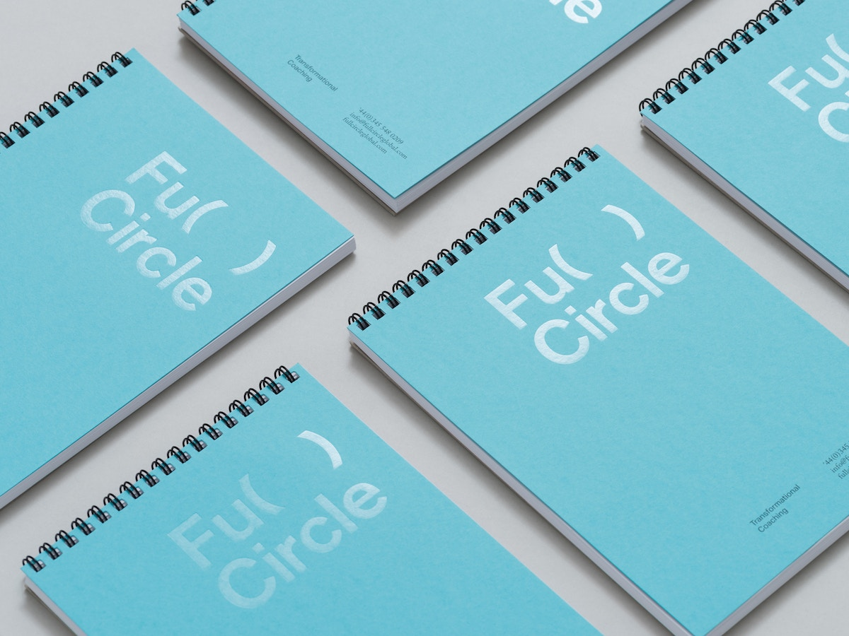 Blue wire bound notebooks with the Full Circle logo on them.