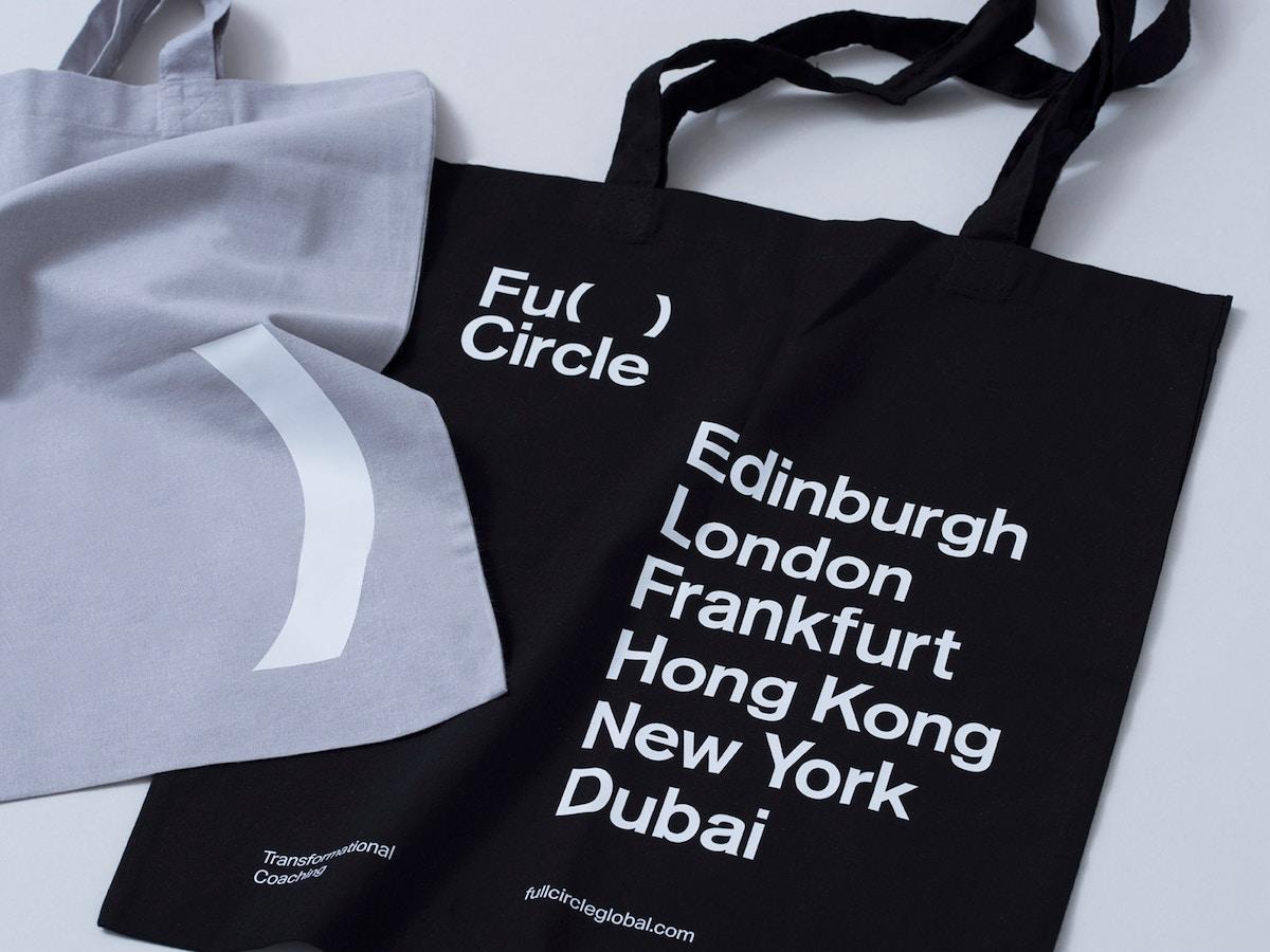 "A grey tote bag sits over a black tote bag. The black tote bag has white text on it that reads ""Full Circle. Edinburgh,London,Frankfurt,Hong Kong,New York,Dubai""."
