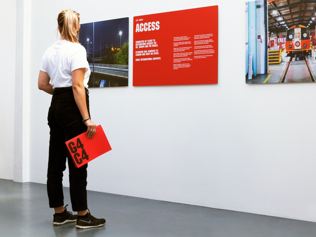 A woman standing in front of a red exhibition board. She is holding a red document.