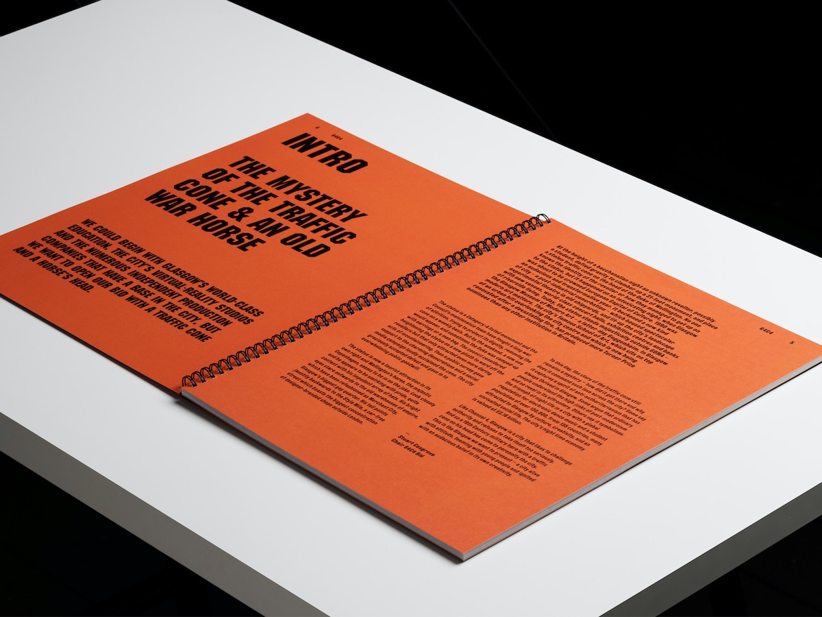 A two page spread made of orange paper. There is black text over both pages.
