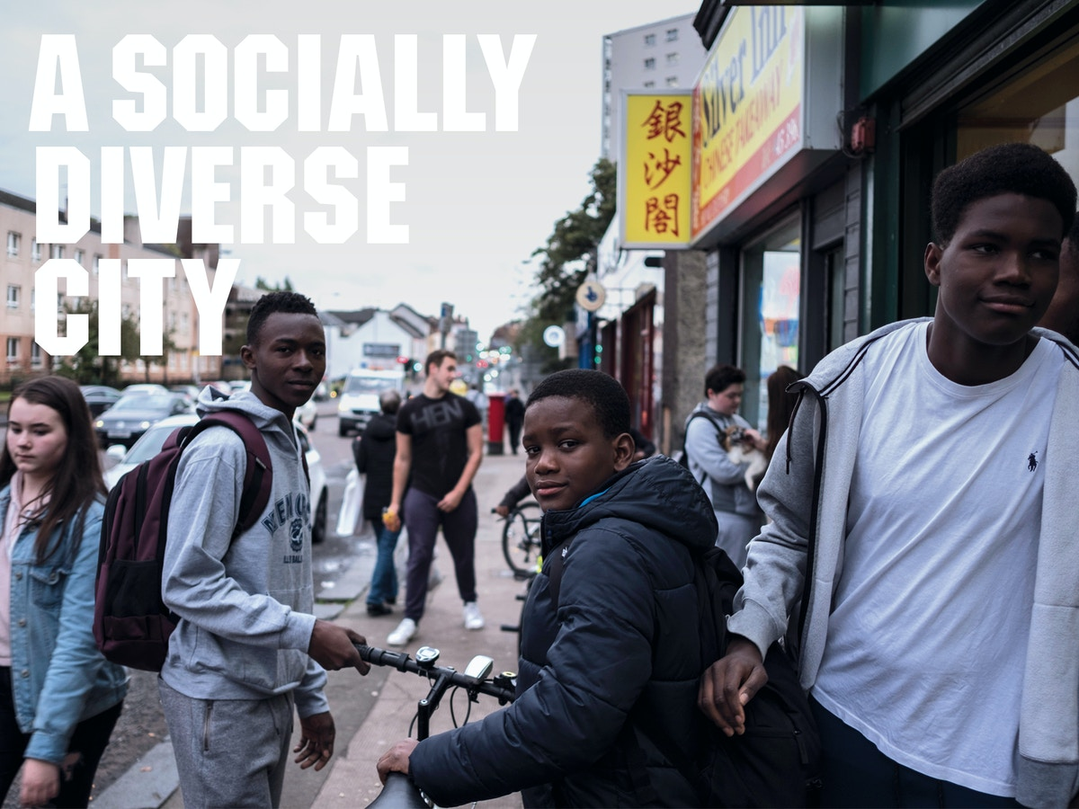 """Text that reads """"a socially diverse city"""" on a background of three boys staring at the camera with other people in the background."""
