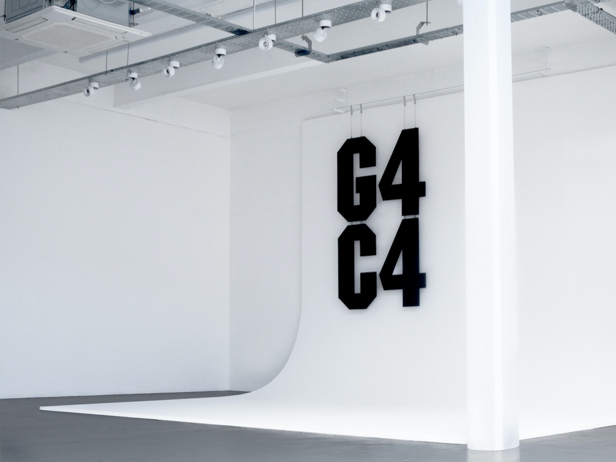 """A white photographic background with large black angular cut lettering that reads """"G4C4"""""""