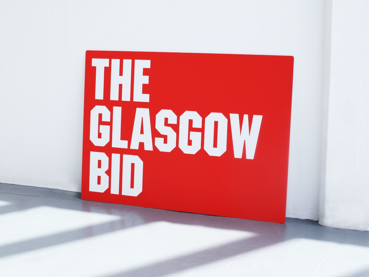 """A large red exhibition panel that reads """"The Glasgow bid"""" in angular, uppercase white lettering."""