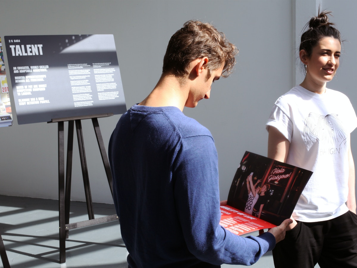 Two people standing in a brightly light space, reading a document.