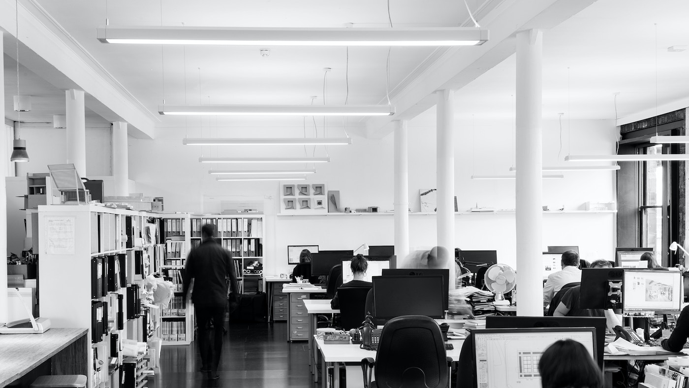People sitting at office desks in a large open plan space. In black and white.