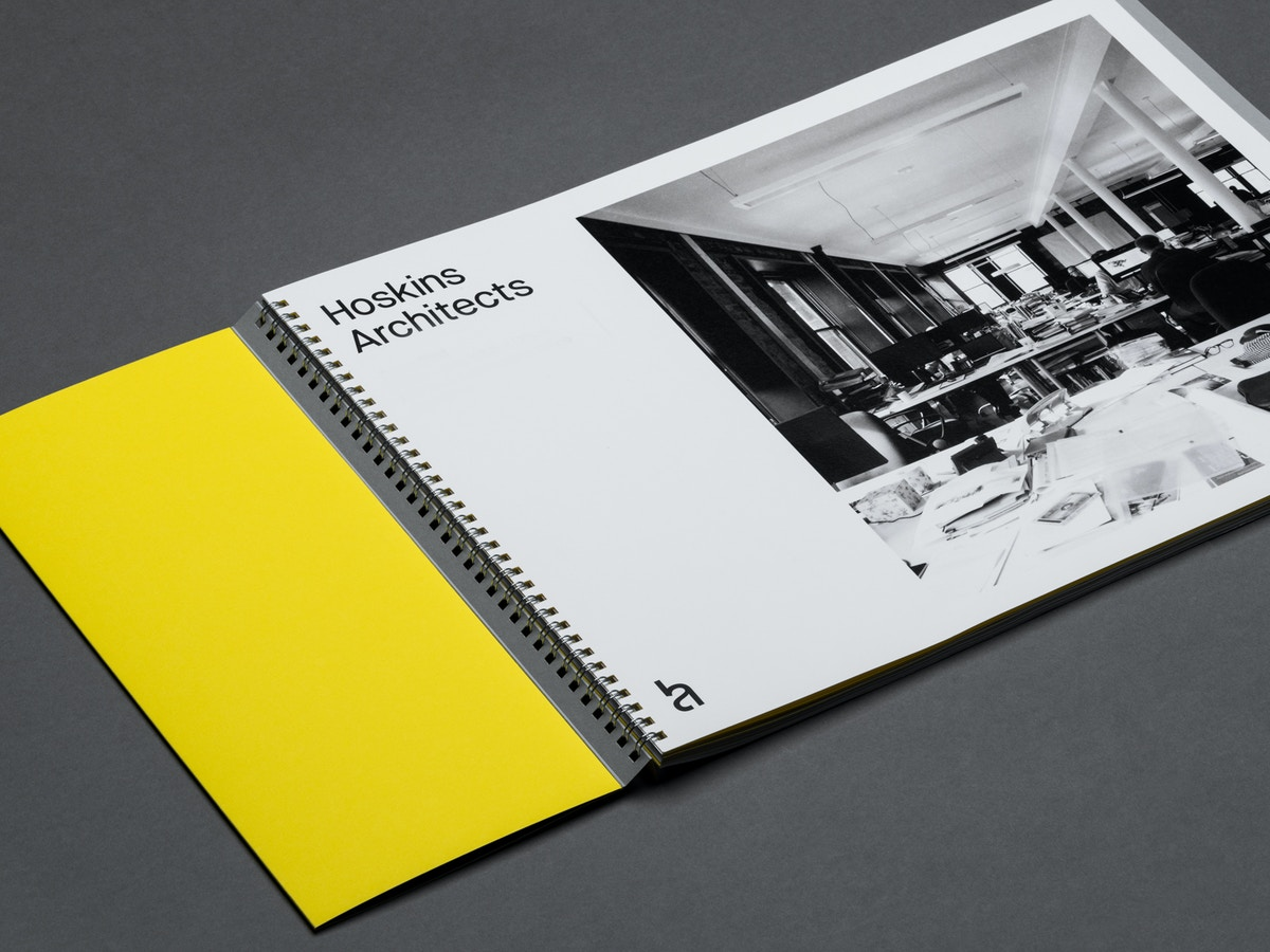Detail of a brochure with a yellow cover and black and white inside.