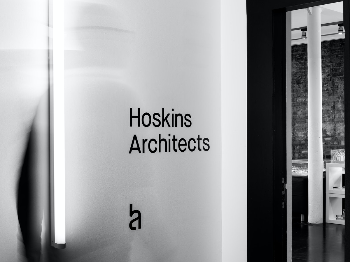 """Black vinyl lettering on a white wall that reads """"Hoskins Architects"""". There is logo below the text."""