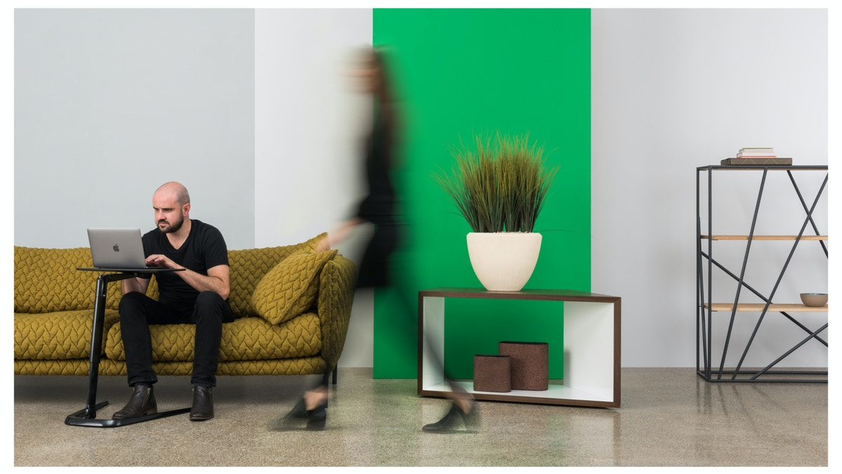 A man sitting on a yellow sofa using a computer. A blurred women is walking by her. There is a green panel in the background.