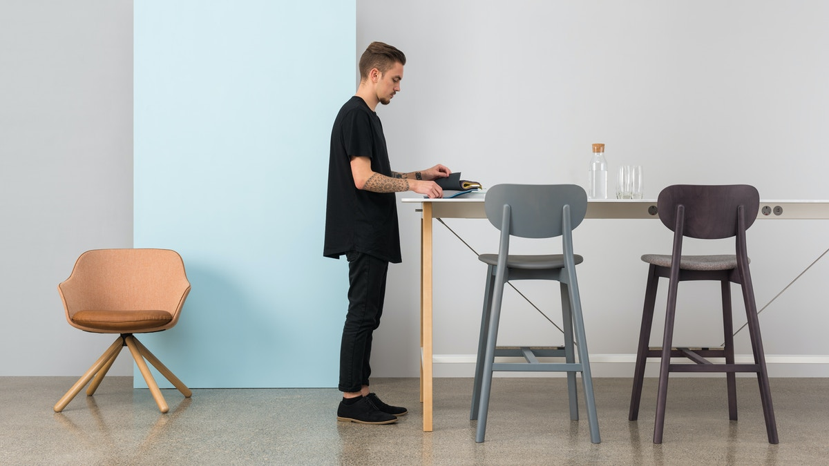 A man places objects onto a tall table. There are two barstools beside him.