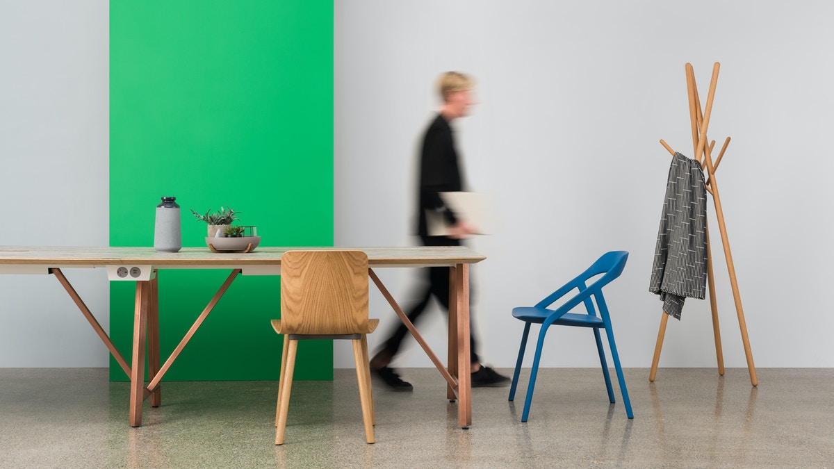 A table and chair set up in front of a green panel. There is a blurred person walking out of shot in the background