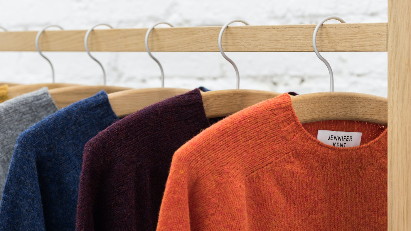 Four jumpers sitting on wooden hangers on a wooden rail. The jumpers are orange, purple, blue and grey.
