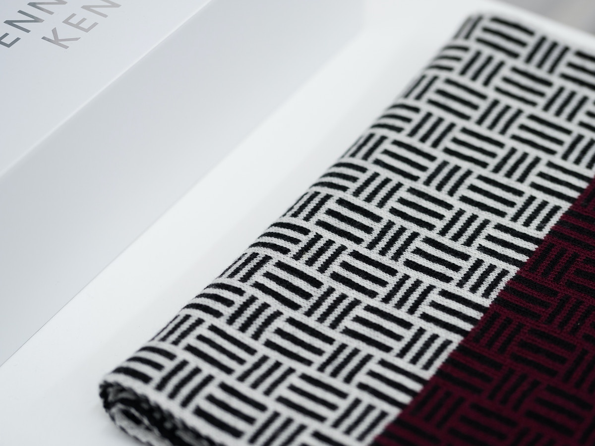 A black and white dash pattern on a scarf that sits next to a white box.