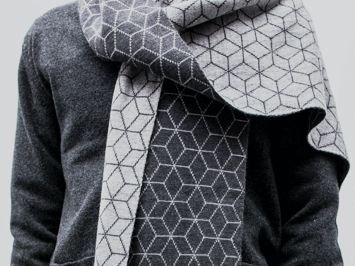 Detail of a man wearing a grey patterned scarf.