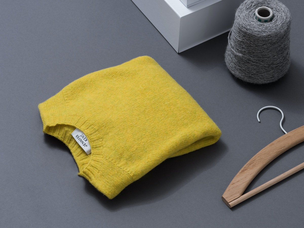 A yellow jumper siting with a wooden hanger and grey loom.
