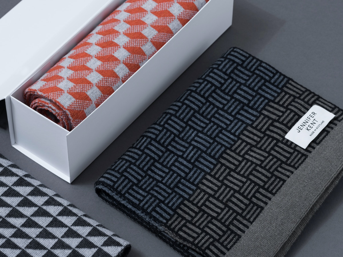 A white box with an orange patterned scarf sitting next to a black and grey patterned scarf.