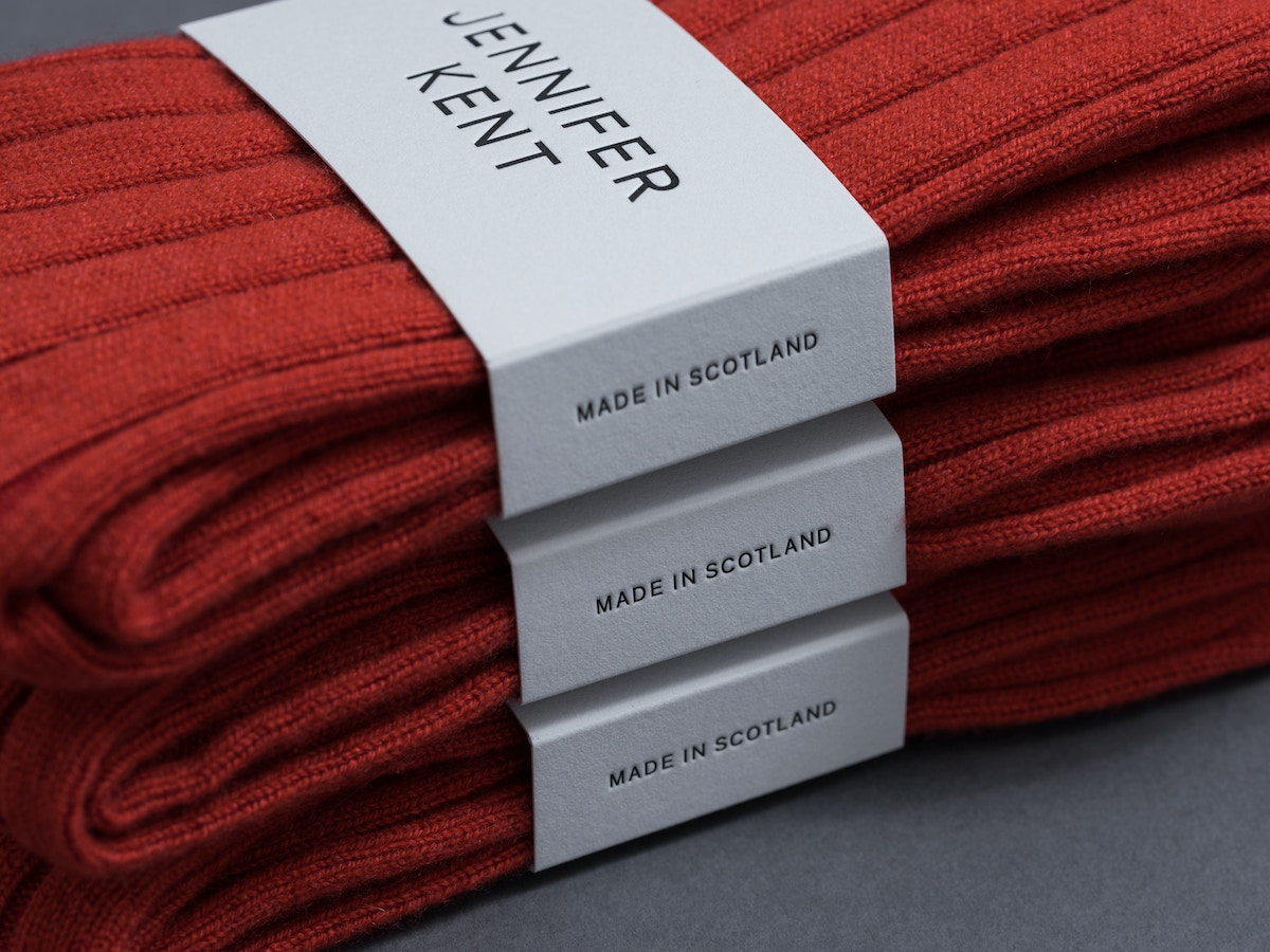 Detail of white packaging sleeve around a red pair of socks. There are three pairs stacked on top of each other.