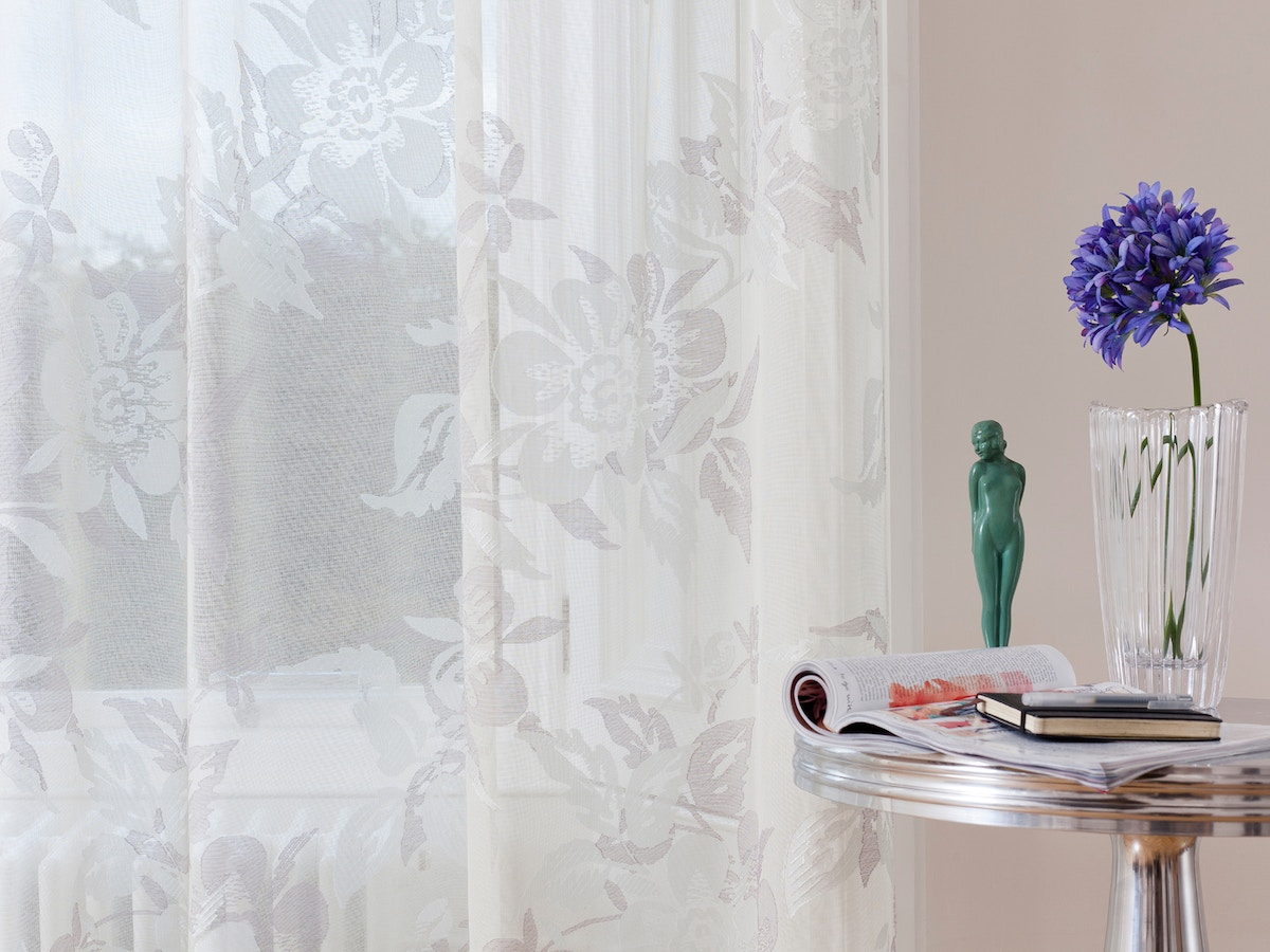 A lace curtain next to a table that has a flower in a vase, an open magazine and a pen and diary on it.
