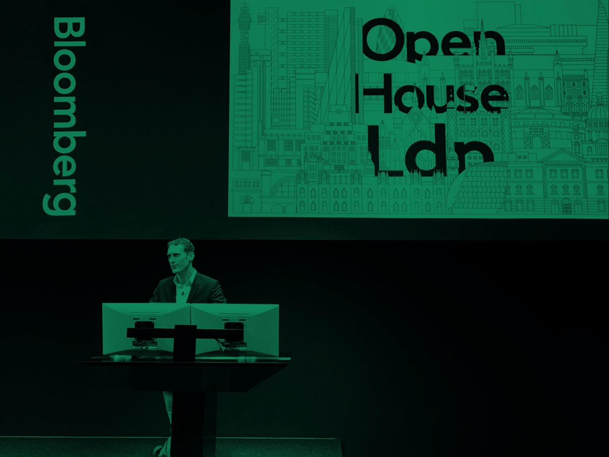 A man stands at a podium in front of a screen that has text on it. The photograph has been washed in green.