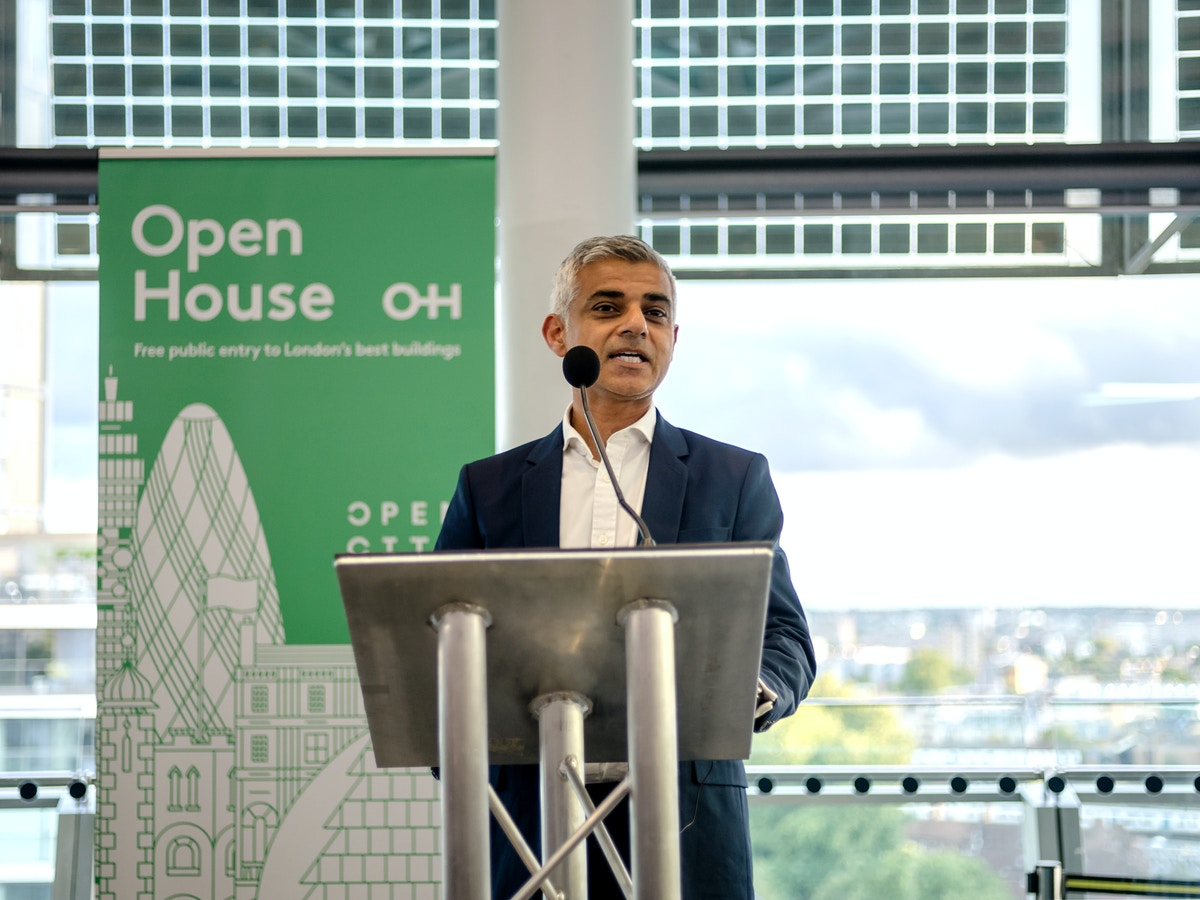 """A man stands at a podium in front of a banner that reads """"Open House"""" and has an illustration of the London skyline on it."""