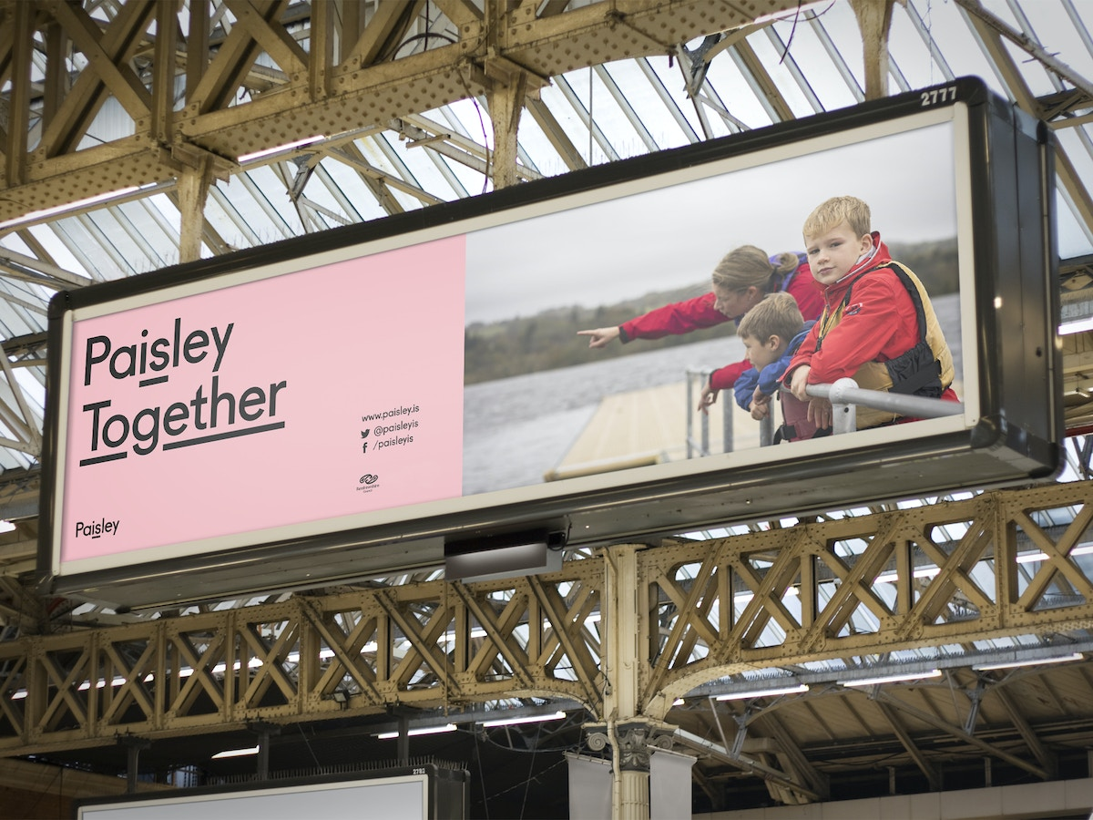 """A billboard advertisement in a train station. The text reads """"Paisley Together"""" set in black type on a pink background."""