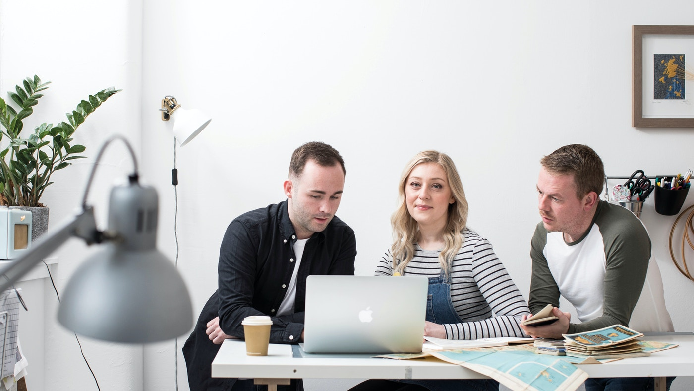 Three people sit at a table in front of a laptop. The woman in the middle has blonde hair and looks at the camera.