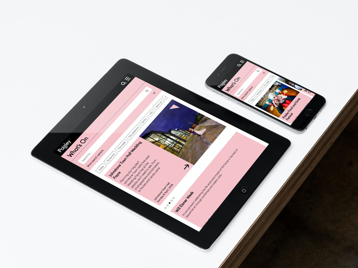 A mockup of a website shown on an iPad and an iPhone that are sitting on a white tabletop.