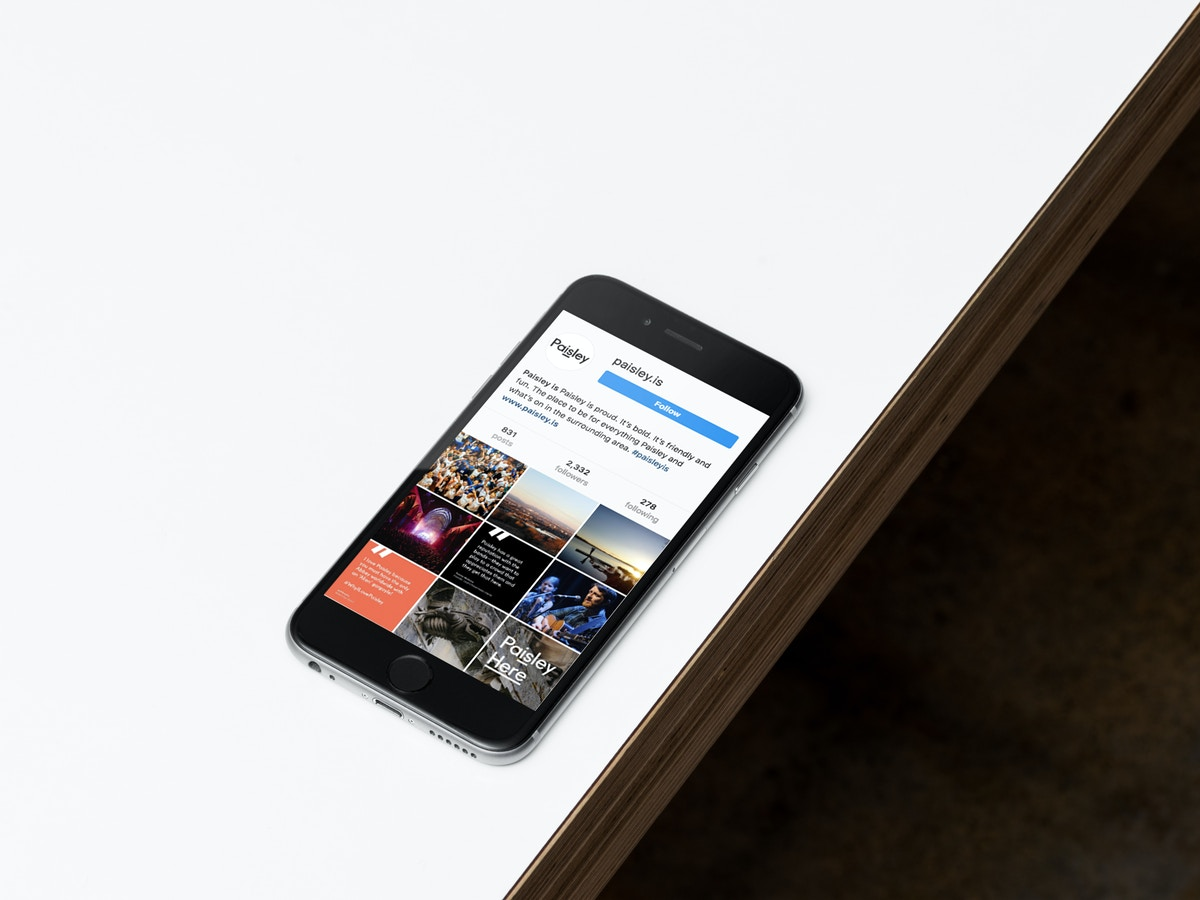 A mockup of a social media page on an iPhone that sits on a white tabletop.