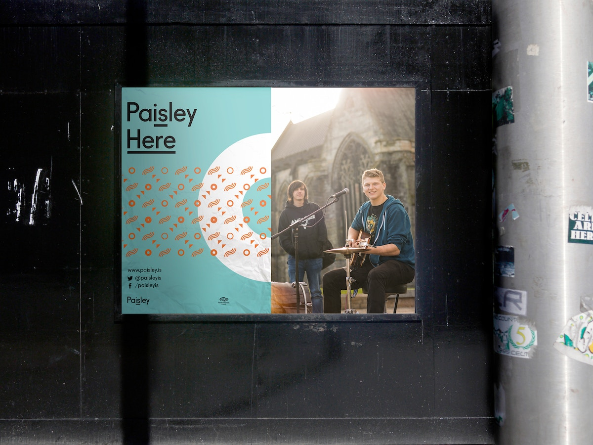 """A poster that reads """"Paisley. Here"""" with a circular shape in the background next to a poster of musicians."""