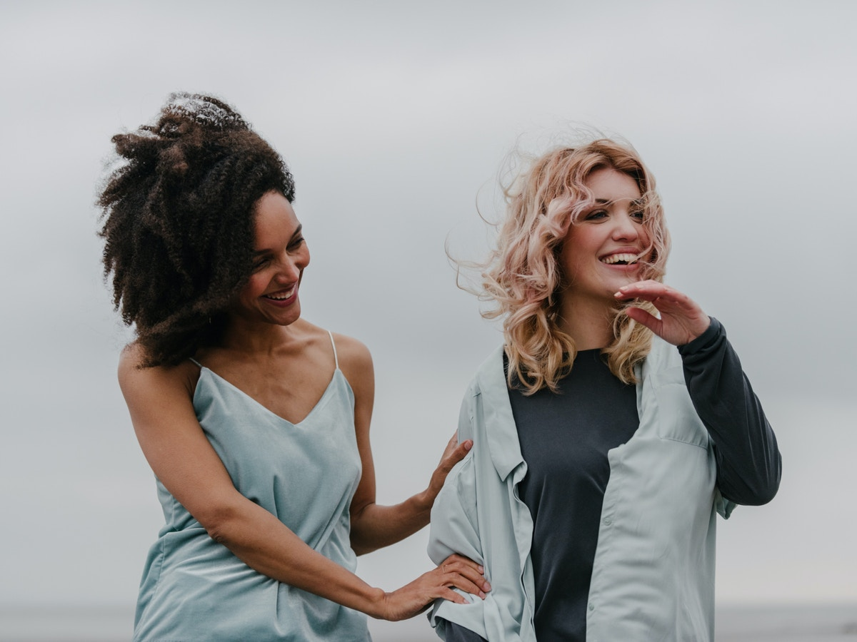 Two women laughing. Their hair appears to be blowing in the wind. The woman on the left is holding onto the others arm.