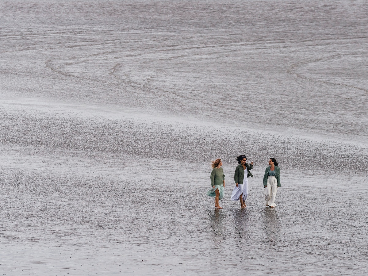 Three women walking beside each other along a beach. There is only sand visible behind them.
