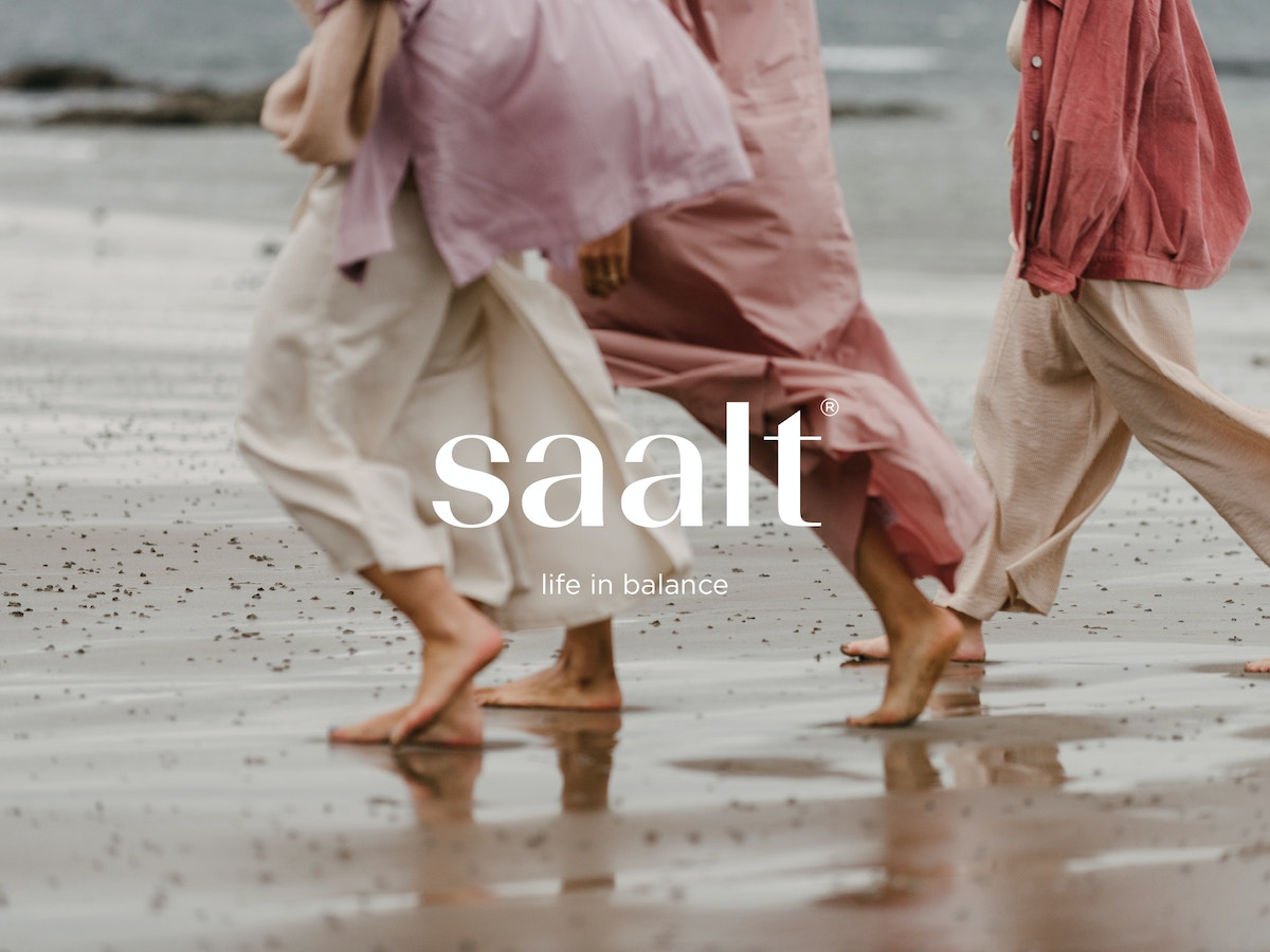 "Text that reads ""Saalt. Life in balance"" over a photograph of three women walking barefoot along a beach. They are all wearing pinky red shades of clothes."